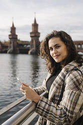 Portrait of a woman with smartphone in the city at Oberbaum Bridge, Berlin, Germany - AHSF01236