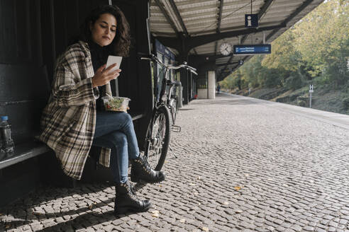 Woman with bicycle having lunch and using smartphone on station platform, Berlin, Germany - AHSF01242