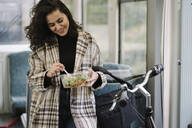 Young woman with bicycle having a lunch on a subway - AHSF01245