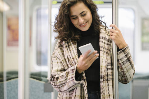 Smiling young woman using smartphone on a subway - AHSF01248
