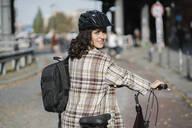 Portrait of woman with a bicycle in the city, Berlin, Germany - AHSF01254