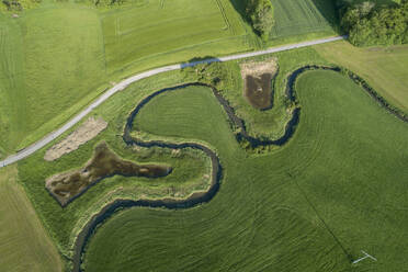 Germany, Bavaria, Aerial view of green countryside fields and meandering Wornitz river - RUEF02371