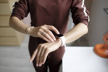 Woman tipping on smart watch at home - KMKF01150