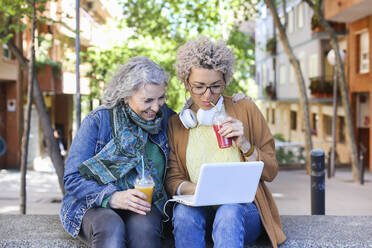 Senior mother with her adult daughter using laptop and drinking juices in the city - RTBF01380