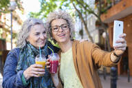 Senior mother with her adult daughter taking selfie in the city - RTBF01386