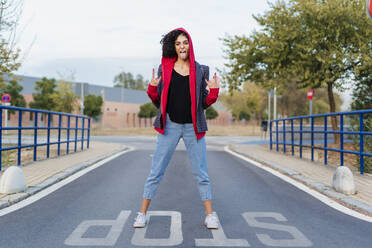 Portrait of young woman standing on  the street sticking out tongue and showing Rock And Roll Sign - ERRF02044