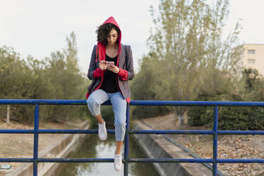 Young woman sitting on railing using mobile phone - ERRF02050