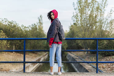 Portrait of young woman with backpack standing on a bridge - ERRF02053