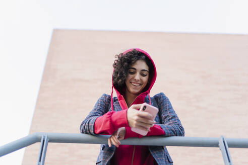 Portrait of happy young woman leaning on railing looking at mobile phone - ERRF02059