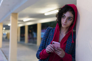 Portrait of young woman with mobile phone in the evening - ERRF02065
