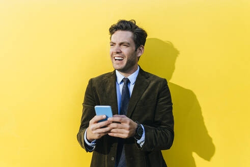 Happy businessman with smartphone in front of yellow wall - KIJF02742