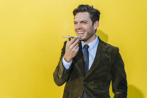 Happy businessman using smartphone in front of yellow wall - KIJF02745