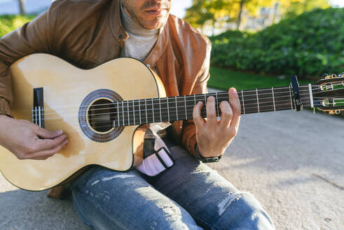 Close-up of man playing guitar in a park - KIJF02766