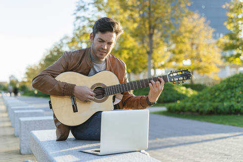 Man with laptop playing guitar in the city, Madrid, Spain - KIJF02769