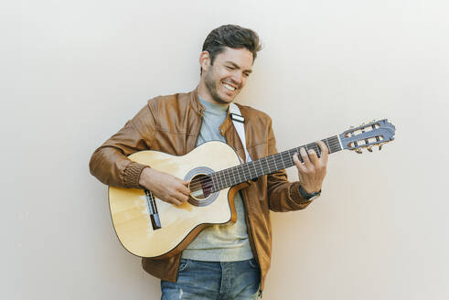Smiling man playing guitar in front of a wall - KIJF02772