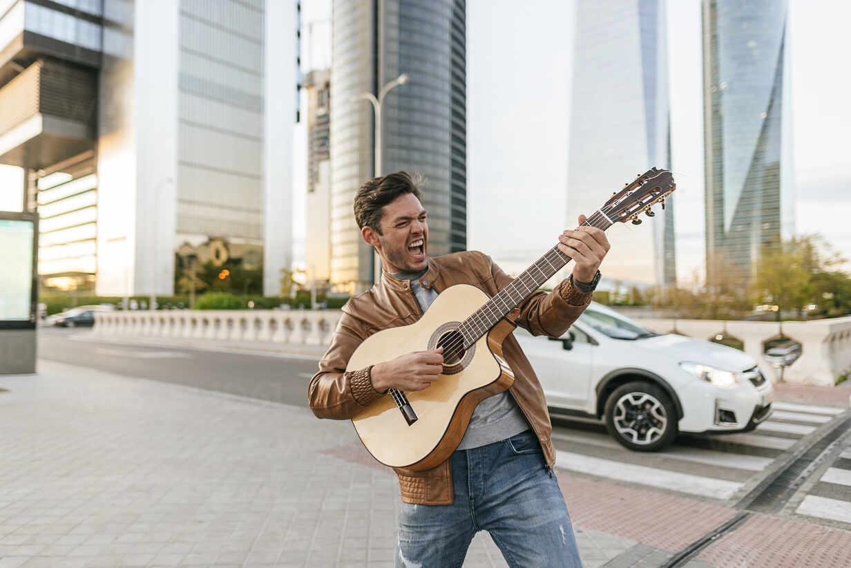 Excited man playing guitar in the city, Madrid, Spain - KIJF02790 - Kiko Jimenez/Westend61