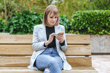 Woman sitting on park bench using cell phone - KIJF02799