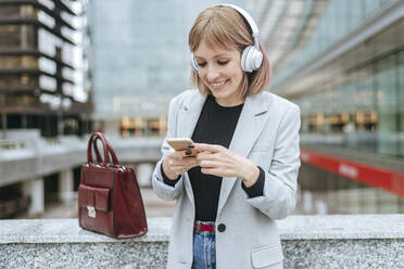 Smiling woman ith smartphone and headphones in the city - KIJF02802