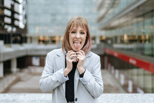 Portait of woman sticking out her tongue in the city - KIJF02805
