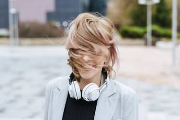 Happy woman with headphones moving her hair - KIJF02808