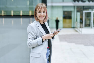 Portrait of smiling woman with cell phone at glass building - KIJF02817