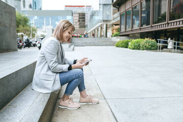 Smiling woman sitting on stairs  in the city using cell phone - KIJF02823