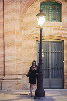 Smiling young woman leaning against street light in the evening looking at cell phone - DLTSF00283