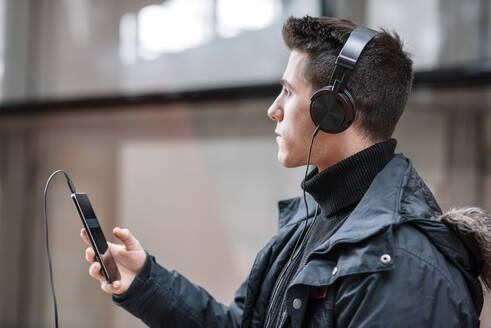 Young man with smartphone and headphones listening to music - DHCF00201