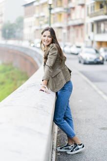 Young brunette woman looking at camera and leaning on a wall - GIOF07731