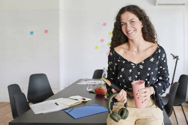 Portait of smiling casual young businesswoman in an office - IGGF01450