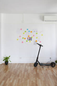 Electric scooter in front of a wall full of sticky notes in a bright modern office - IGGF01459