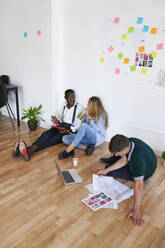 Young business people sitting together in an office having a meeting - IGGF01462