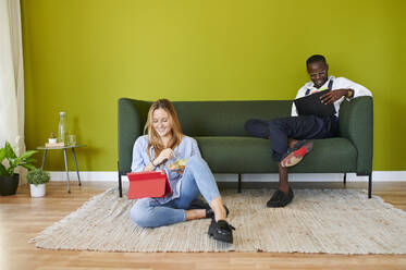 Two smiling young business people sitting in lounge in modern office - IGGF01480