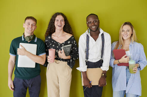 Portrait of happy casual colleagues standing together in front of a green wall - IGGF01486