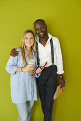 Portrait of smiling casual business couple standing together in front of a green wall - IGGF01489