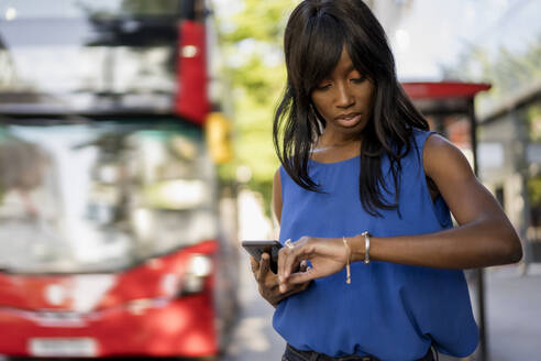 Female Afro-American using smartphone  and checking the time at bus stop in London, United Kingdom - MAUF03065