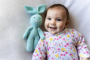 Baby girl with a bunny toy lying on bed - GEMF03308