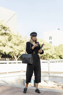 Young blond businesswoman wearing black hat and holding laptop bag and using smartphone - ERRF02075