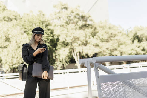 Young blond businesswoman wearing black hat and holding laptop bag and using smartphone - ERRF02078