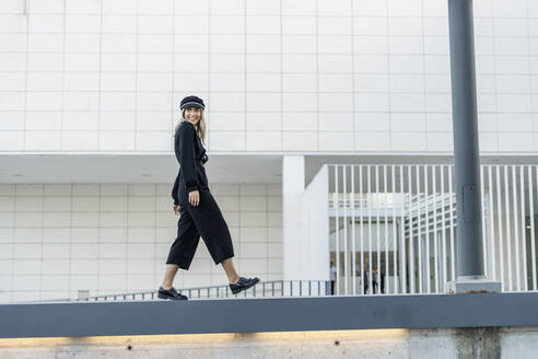 Young blond businesswoman wearing black sailor's cap and walking on a wall - ERRF02099