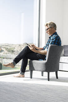 Casual businessman sitting in modern home using tablet - SBOF02035