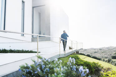 Casual man outside his modern home talking on the phone - SBOF02044