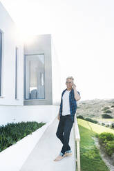Casual man outside his modern home talking on the phone - SBOF02047