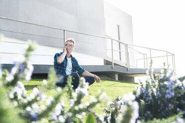 Casual man sitting in front of his modern home talking on the phone - SBOF02050