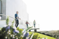 Casual man with his family standing in front of modern home looking at the landscape - SBOF02053