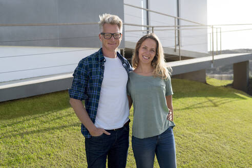 Portrait of smiling couple standing in front of their modern home - SBOF02056