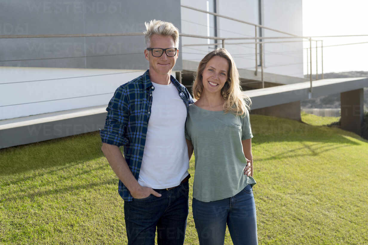 Portrait of smiling couple standing in front of their modern home - SBOF02056 - Steve Brookland/Westend61
