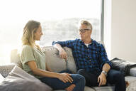 Couple talking to each other on couch in modern home - SBOF02062