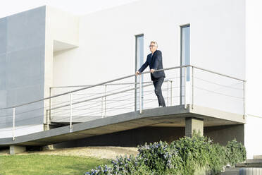 Businessman standing in front of his modern home looking around - SBOF02068