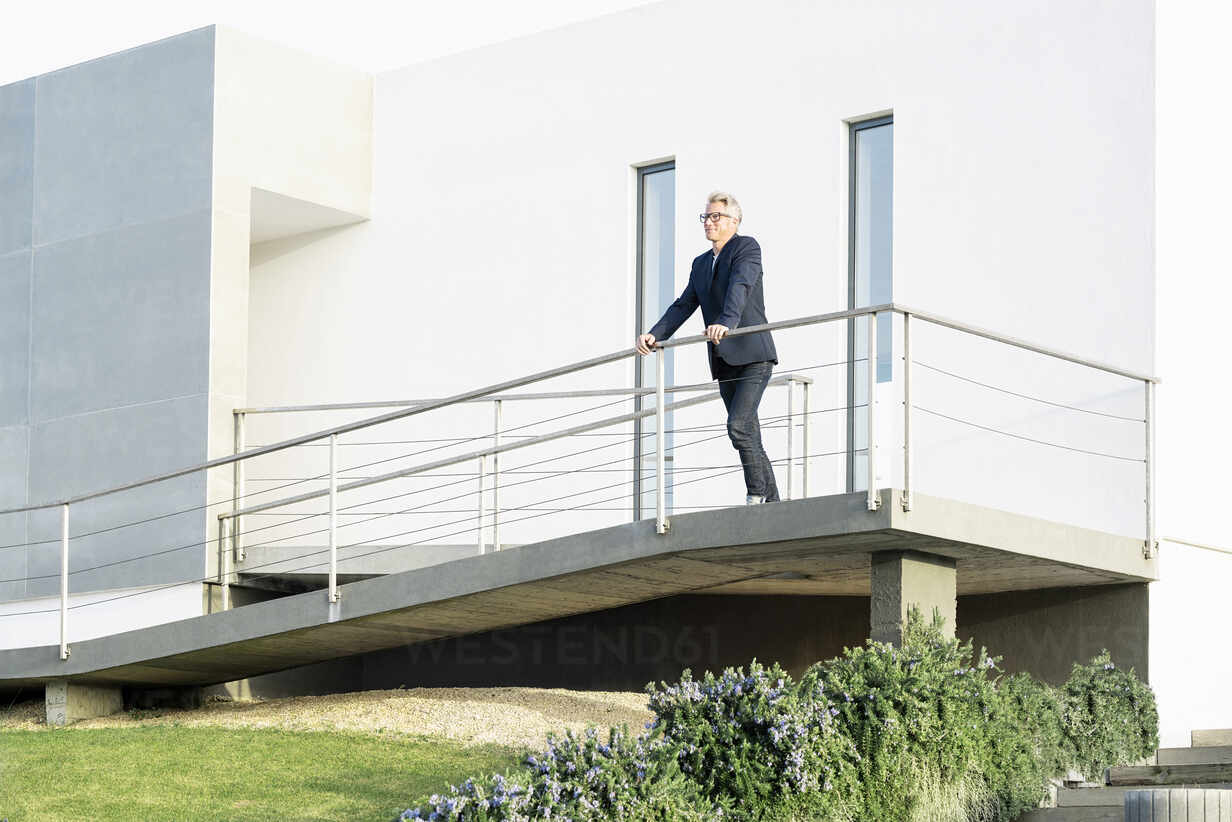Businessman standing in front of his modern home looking around - SBOF02068 - Steve Brookland/Westend61